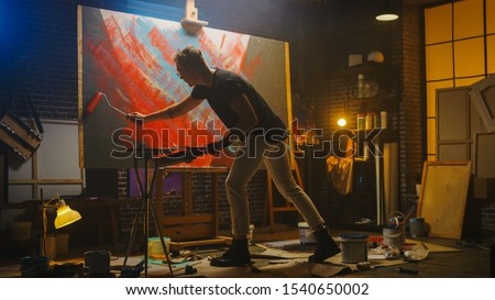 Talented Male Artist Working on a Abstract Painting, Uses Industrial Roller To Create Daringly Emotional Modern Picture. Dark Creative Studio Large Canvas Stands on Easel Illuminated