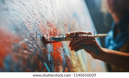 Female Artist Works on Abstract Oil Painting, Moving Paint Brush Energetically She Creates Modern Masterpiece. Dark Creative Studio where Large Canvas Stands on Easel Illuminated. Low Angle Close-up #1540650029