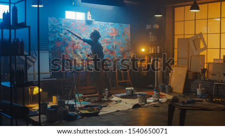 Talented Female Artist Works on Abstract Oil Painting, Using Paint Brush She Creates Modern Masterpiece. Dark and Messy Creative Studio where Large Canvas Stands on Easel Illuminated