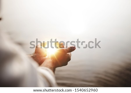 A beautiful shot of Jesus Christ holding hope and light in his palms with a blurred background