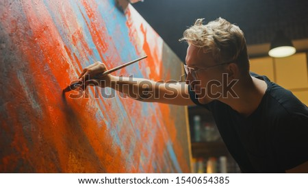 Portrait of Artist Working on Abstract Painting, Uses Paint Brush To Create Daringly Emotional Modern Picture. Dark Creative Studio Large Canvas Stands on Easel Illuminated. Side View Close-up Shot
