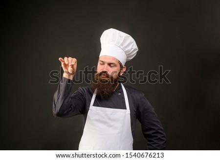 Handsome bearded chef in uniform spilling salt. Man chef in restaurant kitchen preparing food adding salt. Male chef sprinkling salt Bae. Cook man sprinkling salt. Ingredients. Professional kitchen. #1540676213