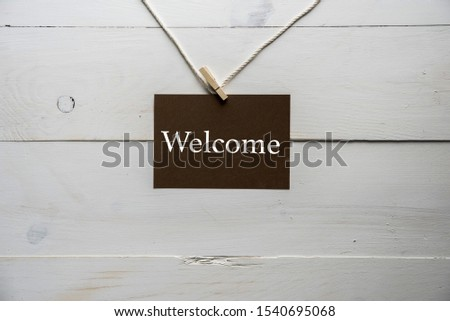 A closeup shot of a sign with welcome written on it and a white wooden background
