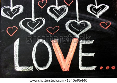 The inscription on the blackboard with chalk. Valentine`s day theme. Dark grunge texture blackboard. Love. I love you. Message of love. The inscription on the blackboard with chalk. Valentine`s day .