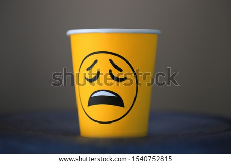 Sad emotion emoji on a paper cup with coffee in the office. Boring office work.