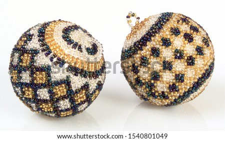 A pic of two blue white and gold beaded balls Christmas tree decorations