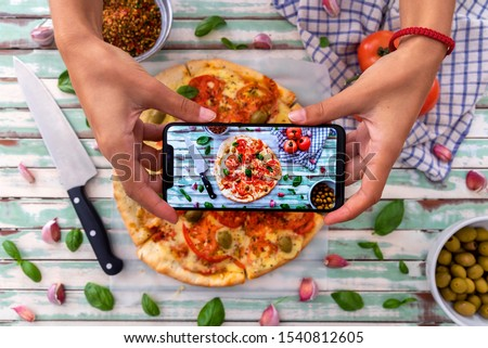 Woman taking pictures of a made wood fired pizza viewed from above on rustic turquoise boards