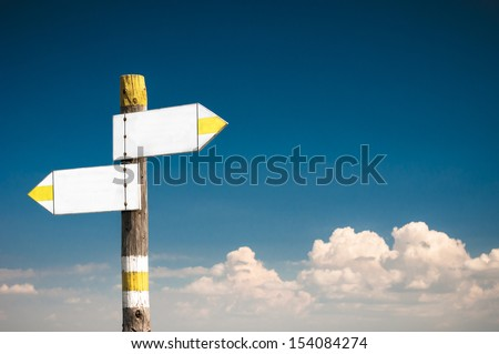 Blank white arrow road sign at the blue sky