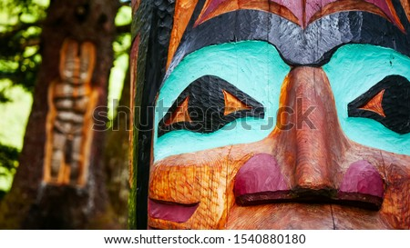 Closeup of colorful Alaskan totem pole in a forest in Juneau and Native art carving on live tree trunk as blurred background #1540880180