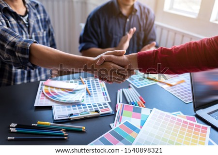 Group of Asian designers shook hands after meeting after choosing the color of the finished product. Happy Concept. #1540898321