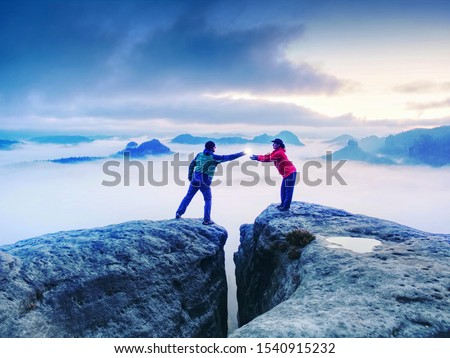 Hikers or climbers in mountains. Couple hold the light  high above danger gulch between rocks. Night photo in misty mountains. Lovers standing on rocky mountain peak #1540915232