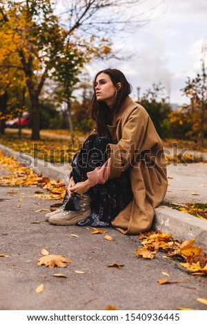 Photo of a sad cute young student brunette girl sitting on border outdoors in nature park with beautiful sunlight look at camera. Autumn walk. Woman wear beige coat, black floral dress and boots.
