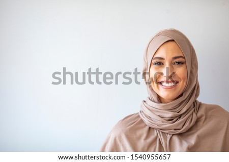 """Modern, Stylish and Happy Muslim Woman Wearing a Headscarf. Arab saudi emirates woman covered with beige scarf. """"Welcome"""" Face. One women smile with white background  #1540955657"""