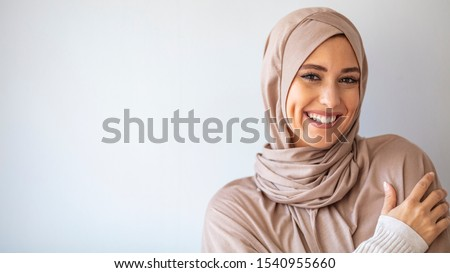 Portrait of islamic woman smiling. Pretty muslim girl. Beautiful asian muslimah woman model posing on grey wall studio. Portrait Of Arab Beauty.  #1540955660