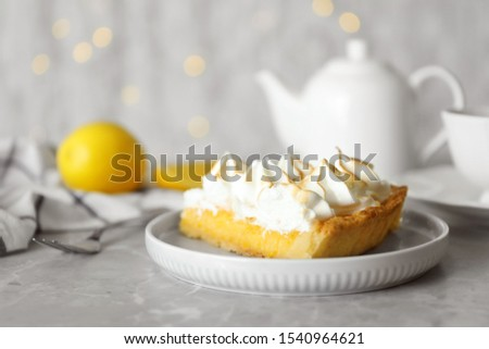 Plate with piece of delicious lemon meringue pie on light grey table