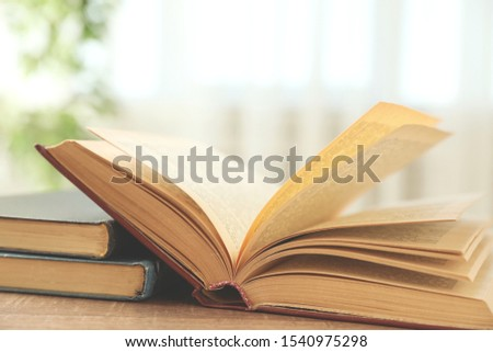 Open hardcover book on wooden table indoors #1540975298