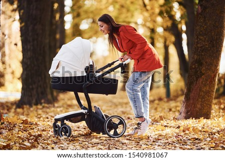 Mother in red coat have a walk with her kid in the pram in the park at autumn time. Royalty-Free Stock Photo #1540981067