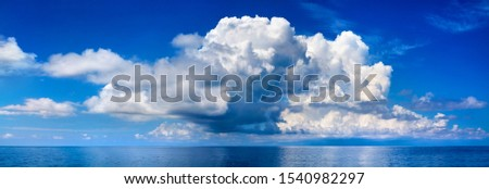 White cumulus clouds in blue sky over sea landscape, big cloud above ocean water panorama, horizon, beautiful tropical sunny summer day seascape panoramic view, cloudy weather, cloudscape, copy space Royalty-Free Stock Photo #1540982297
