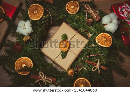 Beautiful Christmas and Happy New Year decorations in closeup.Home decor for winter holidays.Green wreath of pine tree branches decorated with dry oranges and cinnamon sticks for front door decoration