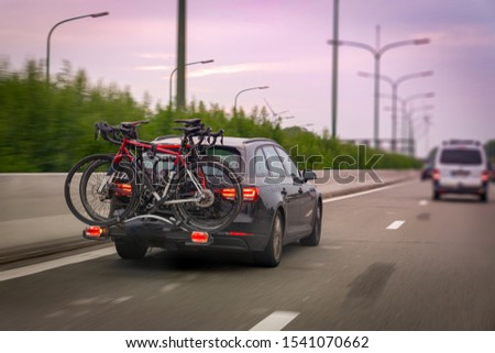 Car transports bicycles on a rack on highway in early morning Royalty-Free Stock Photo #1541070662