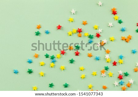 Sprinkle background with bright colourful star sprinkles scattered on pale green background with space for text #1541077343