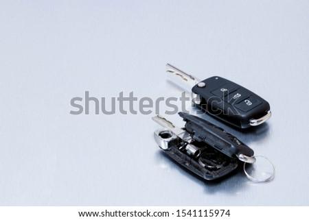 Locksmith broken or damaged car key fob and new remote vehicle key on aluminium background. Repair of broken or damaged remote key fob of any vehicle car service.- Image #1541115974