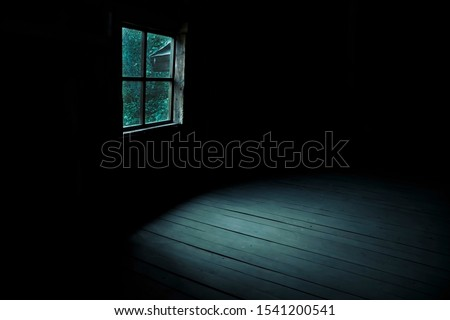 Abstract horror background for halloween. Gloomy scary terrible window with ghostly light and shadows in a dark black room in the attic, corridor or basement in an abandoned house in the forest Royalty-Free Stock Photo #1541200541