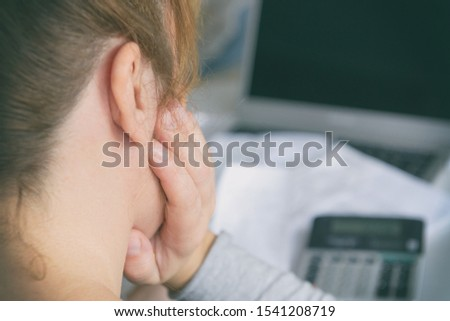 Woman uses a calculator to sum up expenses and holds her head worrying about the amount of money spent #1541208719