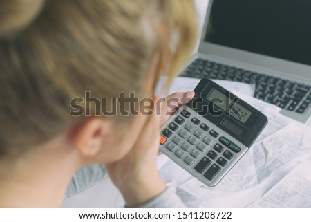 Woman uses a calculator to sum up expenses and holds her head worrying about the amount of money spent #1541208722