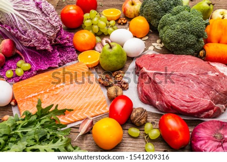 Trending paleo/pegan diet. Healthy balanced food concept. Set of fresh products, raw meat, salmon, vegetables and fruits. Old wooden boards background #1541209316