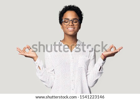 Head shot close up calm African American young woman in glasses meditating, beautiful girl with closed eyes and toothy smile practicing yoga, stress relief concept, isolated on grey background Royalty-Free Stock Photo #1541223146