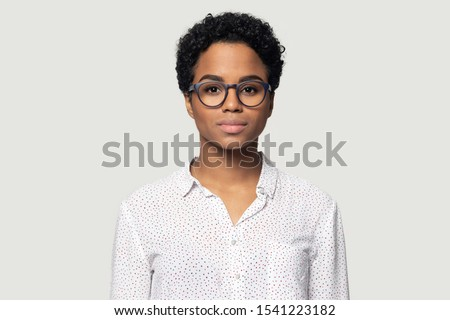 Head shot portrait close up beautiful young African American woman in glasses, businesswoman, student wearing shirt looking at camera, girl with perfect skin, isolated on grey background
