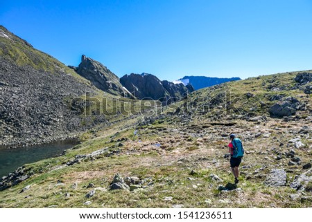 A young woman with a big hiking backpack standing next to a clear, navy blue lake hiding between tall mountain peaks. Some of the slopes are covered with snow. In the back is another mountain range. #1541236511