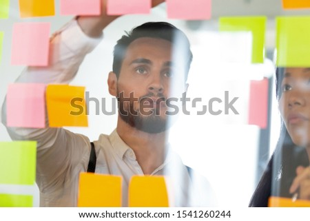 Focused businessman looking at colorful sticky papers on glass wall close up, brainstorming in office, working on project, diverse colleagues discussing strategy, sharing creative startup ideas #1541260244