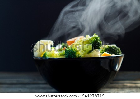 Vegetables, I steaming. Boiled hot Healthy food on table on black background. hot food concept. #1541278715