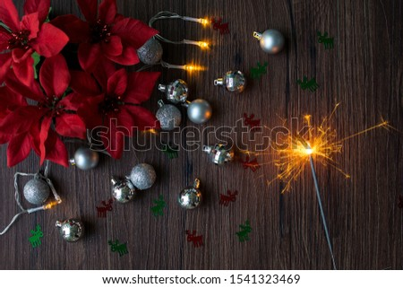 Christmas flat lay decorations with sparkle lighted up. Reindeer cut outs in red and green. Christmas red flowers
