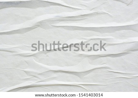 White sheet of crumpled paper glued to the wall. #1541403014