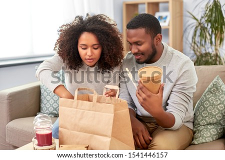 eating and people concept - happy african american couple with takeaway food and drinks at home #1541446157