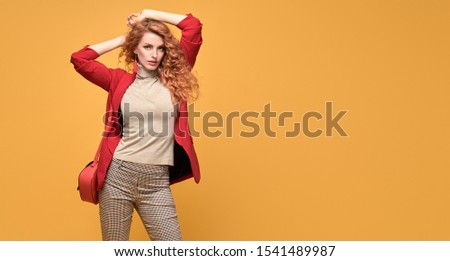 Fashion. Beautiful woman in autumn red jacket, trendy curly hair, make up. Adorable well dressed redhead girl on orange. Gorgeous fashionable lady in red, hairstyle, makeup. Creative beauty shot #1541489987