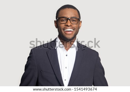 Head shot portrait close up smiling successful African American businessman looking at camera, laughing, excited man wearing formal suit and glasses isolated on grey studio background #1541493674