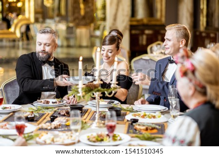 Elegantly dressed group of people having a festive dinner at a well-served table with tasty dishes during New Year Eve at the luxury restaurant #1541510345