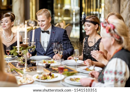 Elegantly dressed group of people having a festive dinner at a well-served table with tasty dishes during New Year Eve at the luxury restaurant #1541510351