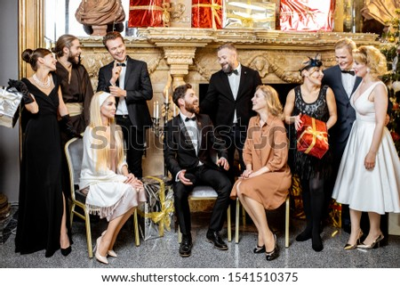 Staged group photo of an elegant well-dressed people near the beautifully decorated fireplace with christmas tree and presents during a New Year celebration #1541510375