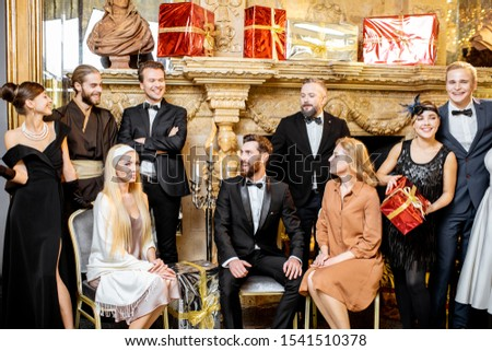 Staged group photo of an elegant well-dressed people near the beautifully decorated fireplace with christmas tree and presents during a New Year celebration #1541510378