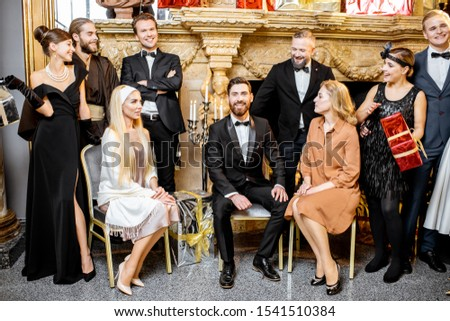Staged group photo of an elegant well-dressed people near the beautifully decorated fireplace with christmas tree and presents during a New Year celebration #1541510384