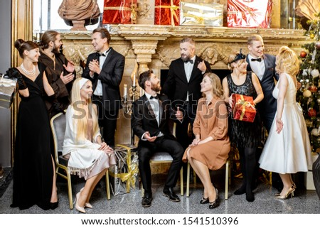 Staged group photo of an elegant well-dressed people near the beautifully decorated fireplace with christmas tree and presents during a New Year celebration #1541510396
