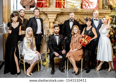 Staged group photo of an elegant well-dressed people near the beautifully decorated fireplace with christmas tree and presents during a New Year celebration #1541510411