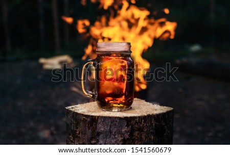 Craft Beer Ale In Mason Jar By Campfire in Woods  #1541560679