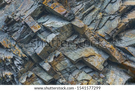 Texture or background layers and cracks in sedimentary rock on cliff fake, selective focus. Cliff of rock mountain, soft focus. Rock slate in the mountain. Cracks of sandstone. #1541577299