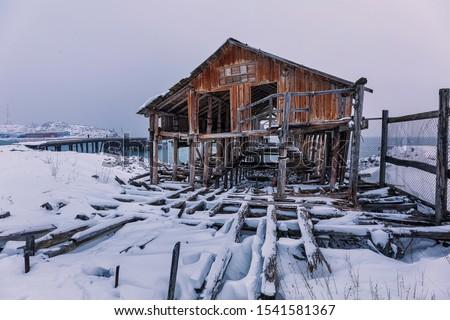 Old abandoned wooden factory against the background of a fish factory. Polar day.  Teriberka, Murmansk district. Kola Peninsula. Russian polar region. Barents Sea #1541581367